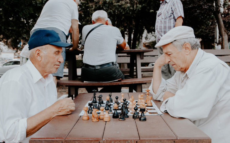 Two older men play chess.