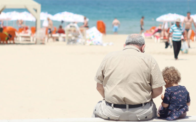 An older man sites at the beach with a child.
