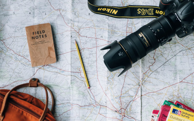 Map with a notebook, pencil and a camera on it.