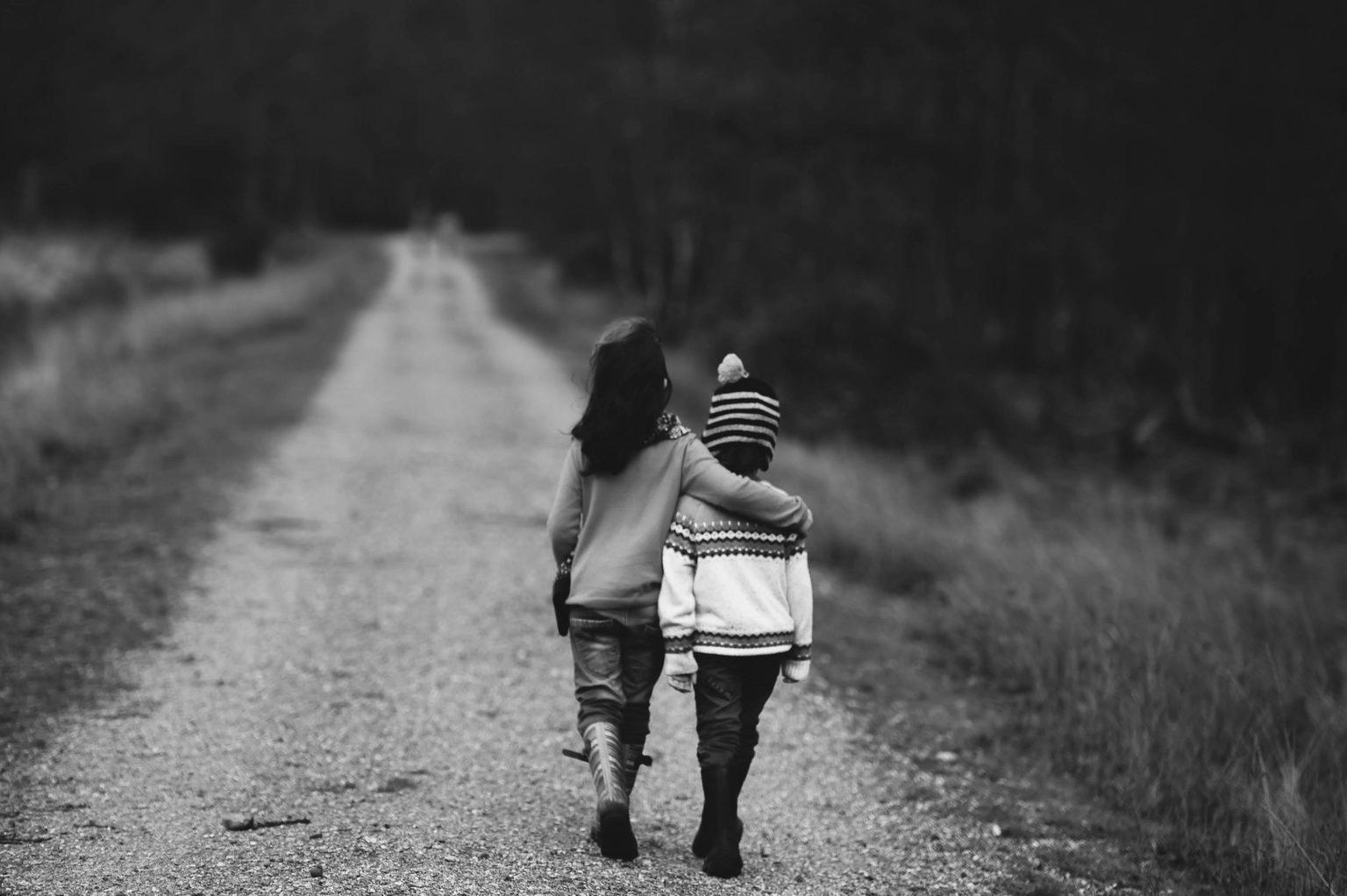 Siblings walking on dirt road