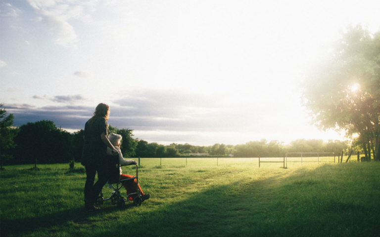 Caregiver and person in a wheelchair looking at the sunset.