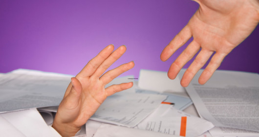 Financial help concept, photo of a hand reaching up from a pile of papers