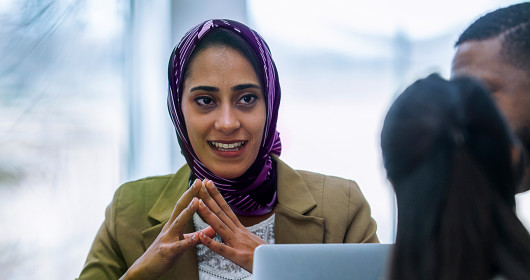 Woman wearing a head scarf talking with a multi-ethnic group of business people in an office boardroom.