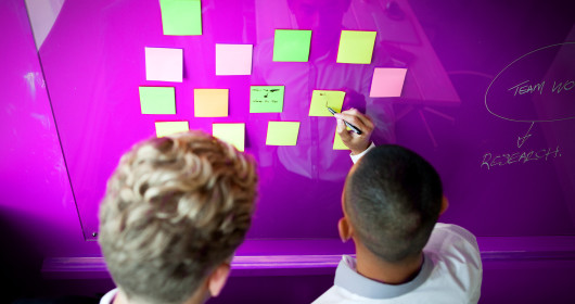 two young business men write on sticky notes