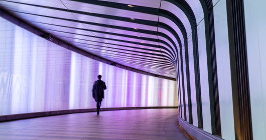 Businessman walking along the illuminated lightwall corridor, connecting One Pancras Square with King's Cross underground station in London