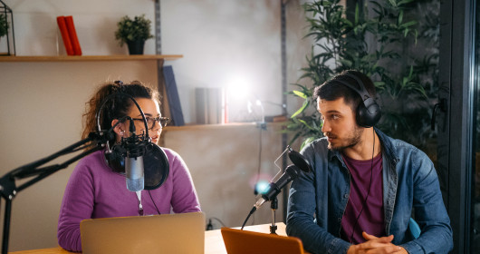 man and woman recording podcast
