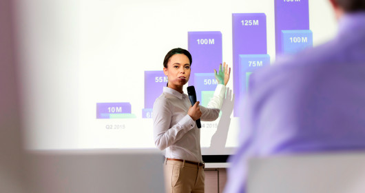 Businesswoman with microphone speaking at projection screen with bar chart