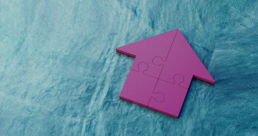 Purple jigsaw house puzzle on blue background