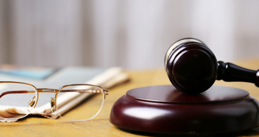 Eyeglasses and a gavel sitting on a table