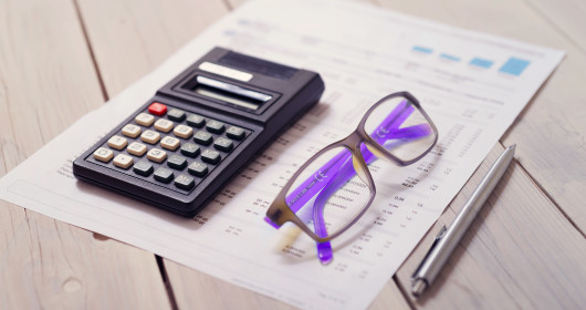 Calculator, pen, eyeglasses and tax forms on wooden table
