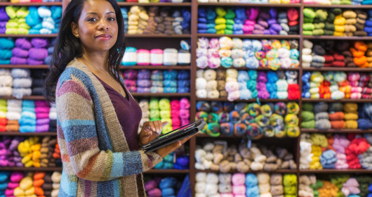 woman in sweater holding digital tablet in yarn store