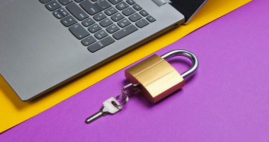 Padlock and key sitting next to open laptop