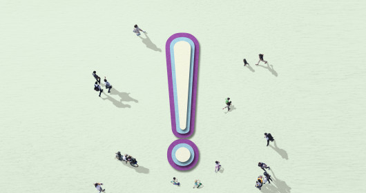 Overhead view of people walking around giant exclamation point