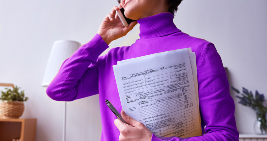 Woman talking on phone and holding tax return paper sheets