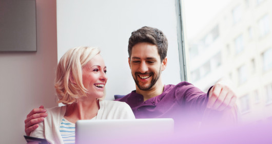 couple smiling in front of laptop computer