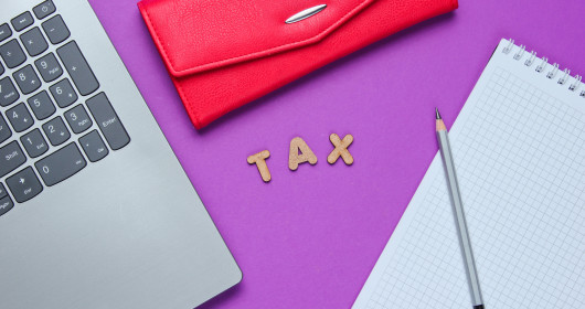 Letters T-A-X laid out on purple background surrounded by desk accessories