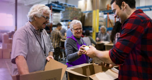 elderly volunteers filling donation boxes in a warehouse