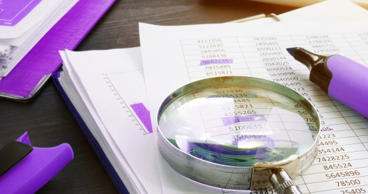 Magnifying glass sitting on top of paper charts