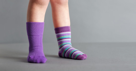 child wearing one purple sock and one striped sock