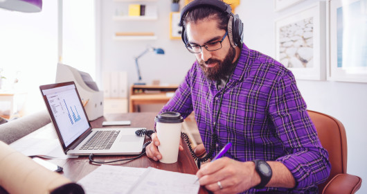 man wearing headphones while working in home office