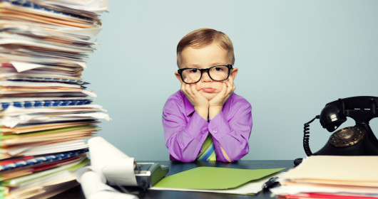 Stressed kid sitting between pile of documents and old fashioned telephone