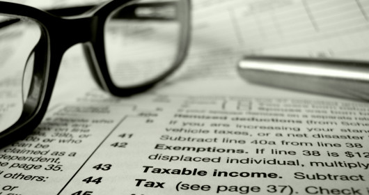 A pen and eyeglasses sitting on top of a tax form