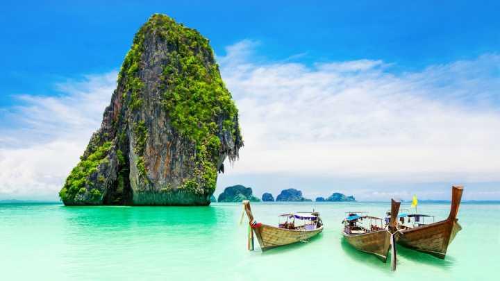 Bateaux amarrés sur l'eau turquoise d'une plage de Phuket en Thaïlande.