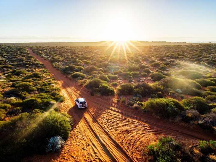 Vue du ciel sur un 4x4 qui traverse le bush australien par une belle journée ensoleillée lors d'une étape d'un circuit de 3 semaines en Australie.