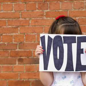School child holding a 'Vote' sign