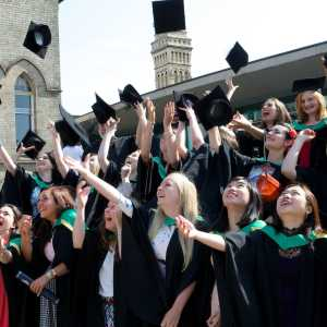 Students at Nottingham Trent University throwing their mortarboards in the air after their graduation ceremony.