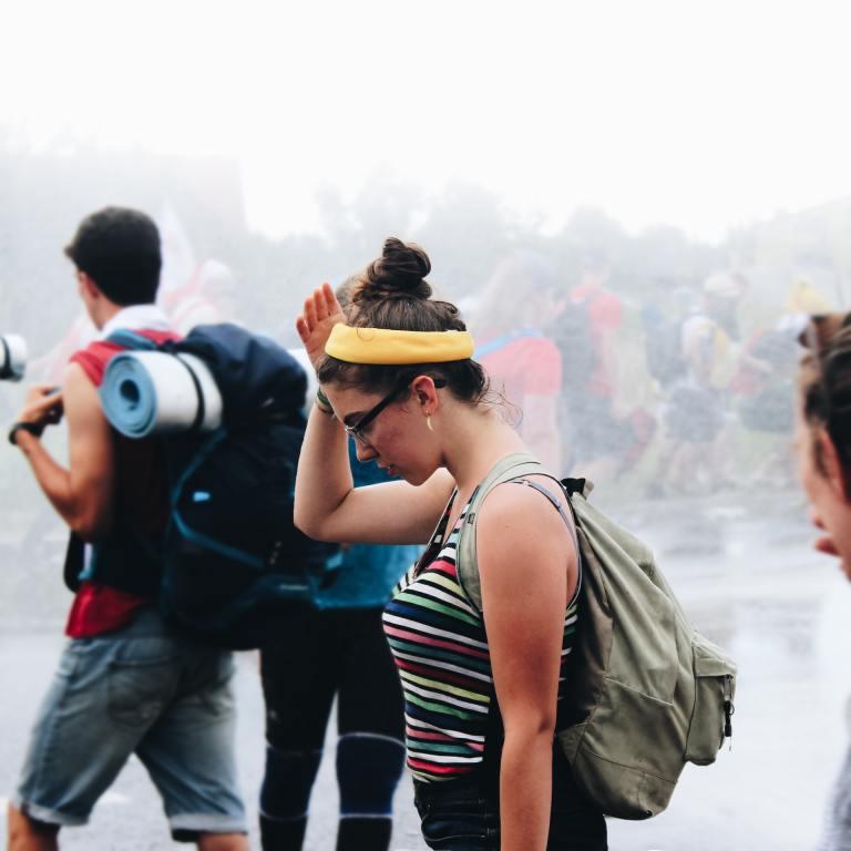 Kobieta z zieloną opaską w deszczową pogodę. Wśród niej znajdują się inni ludzie. Ubrani są jakby byli na wycieczce.