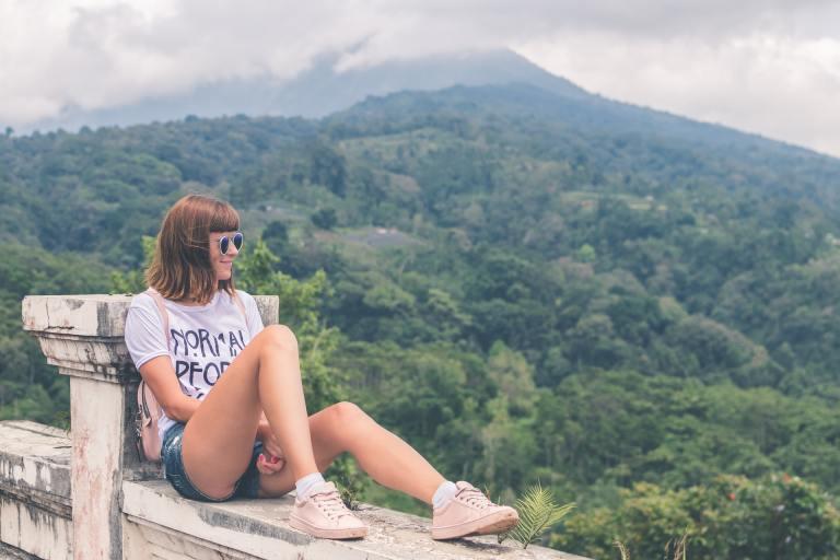 Kobieta w okularach i z prostą grzywką siedząca na murku. W tle widać góry i las.