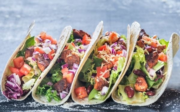 Four tacos with pico de gallo, lettuce, beans, meat and cheese lined up leaning on each other on a table.