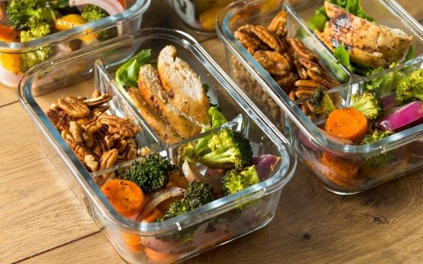 Two glass containers filled with meal prep of chicken, mixed nuts, and assorted vegetables.