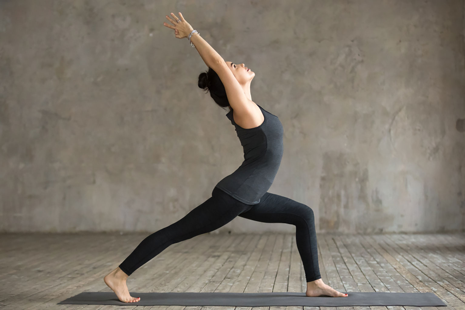 Young woman practicing the high lunge yoga pose