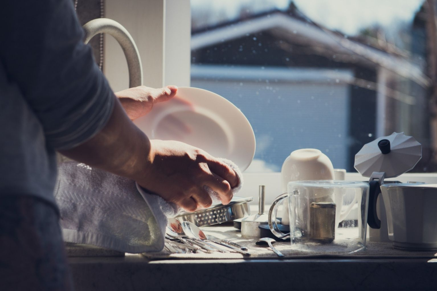 Person cleaning a white plate in their kitchen sink with other clean dishes on the counter