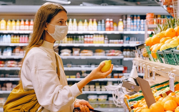woman in a mask shopping for fruit