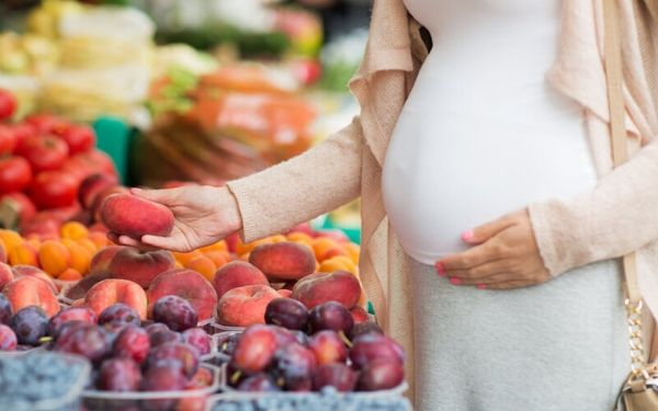 Pregnant woman shopping for fruits at an open air market