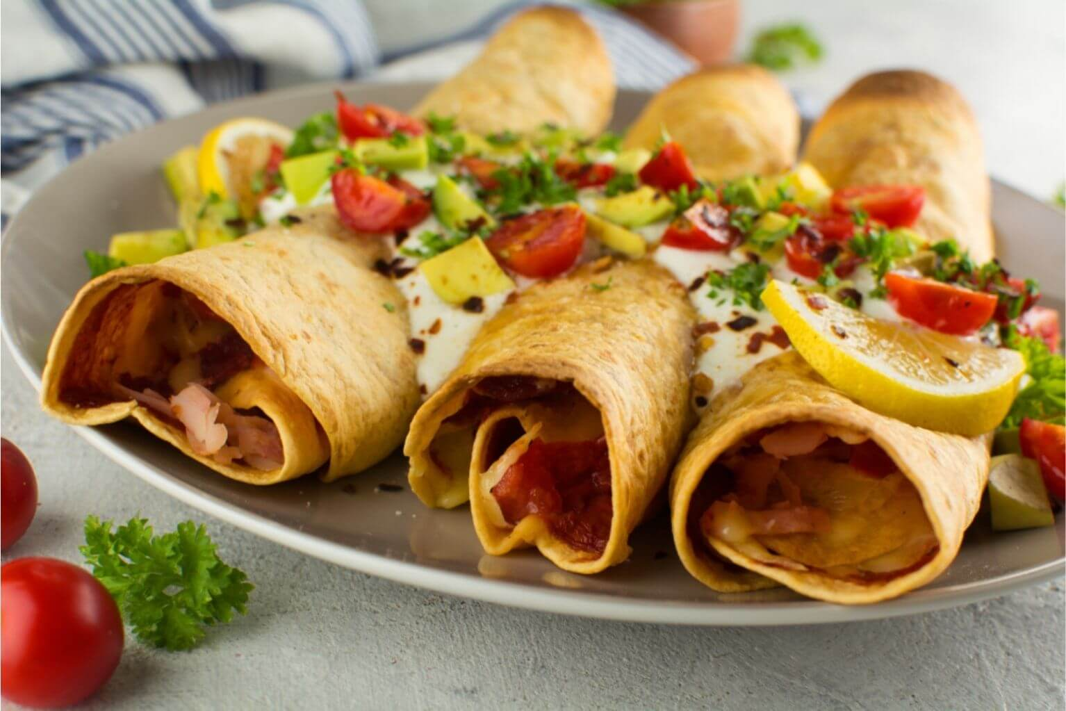 Three taquitos with meat, and cheese inside low carb tortillas on a gray plate on a table.