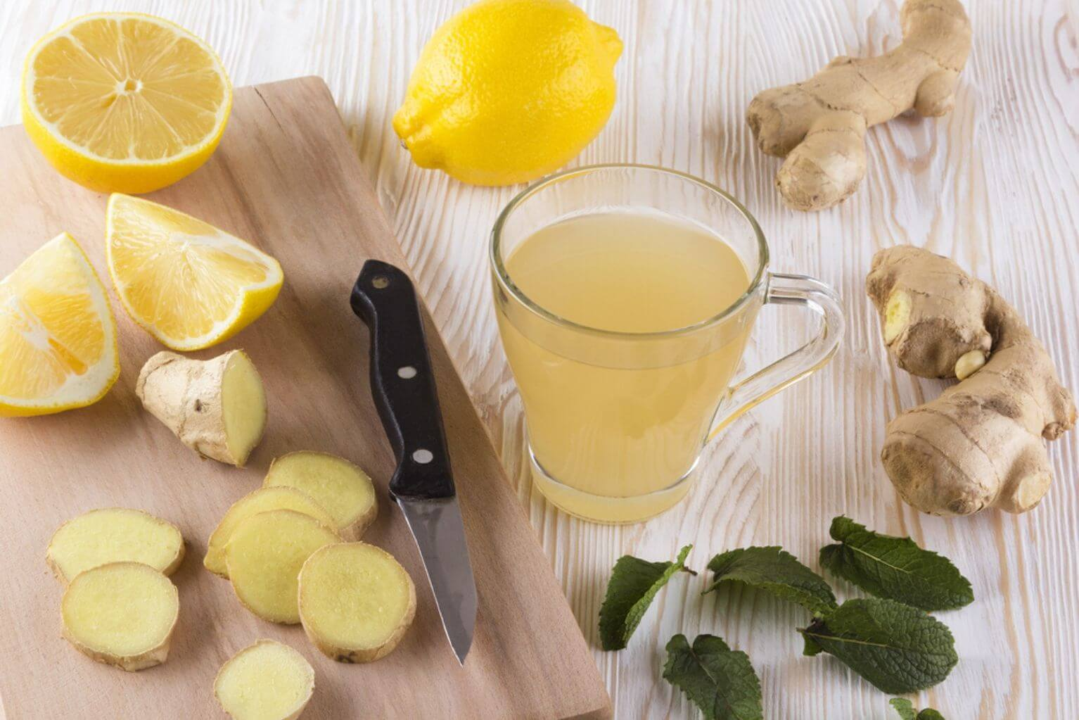 Ginger tea with mint and lemon on a table next to a cutting board and knife