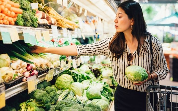 woman shopping at the grocery store holding a head of cabbage and reaching for green onions