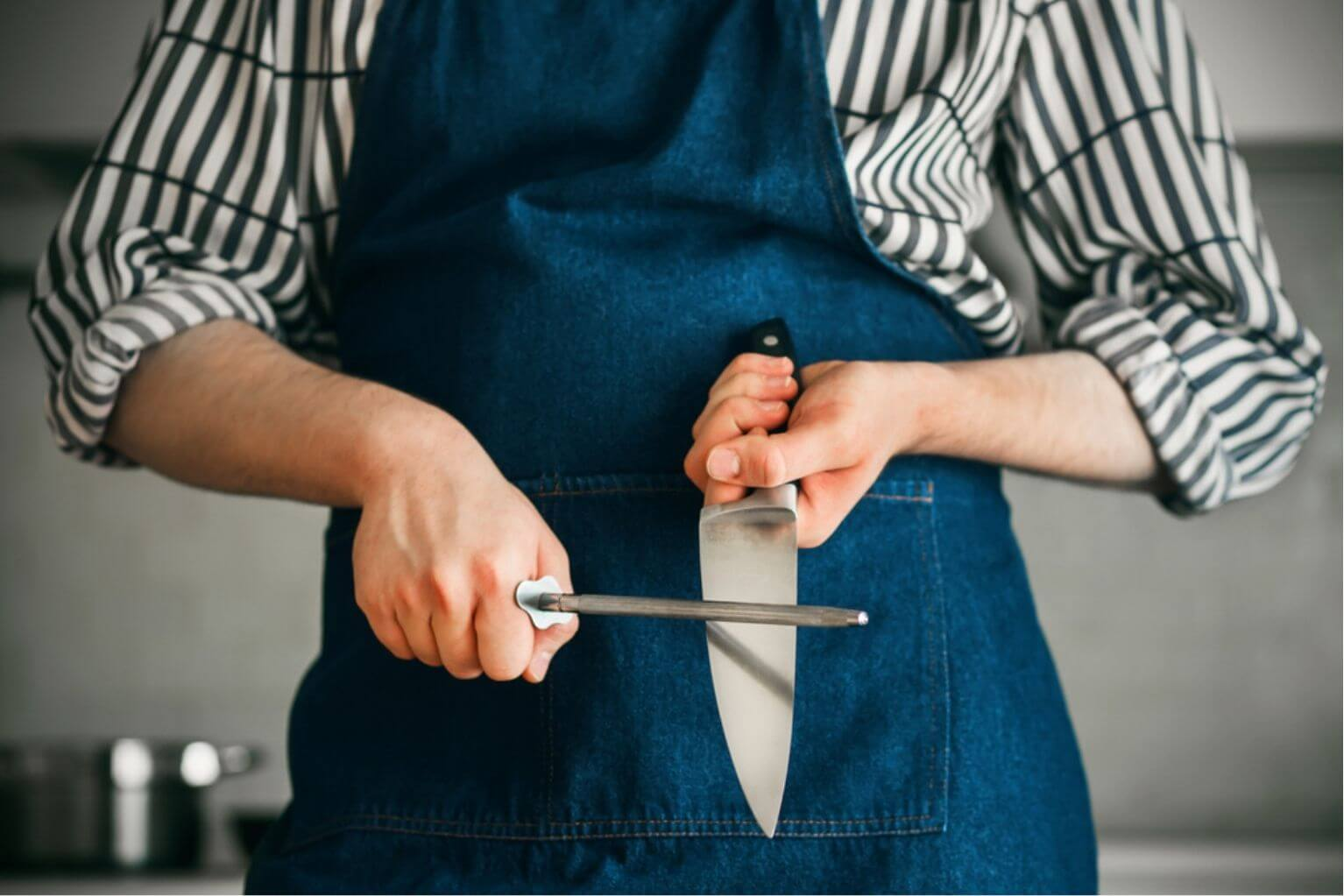 Person wearing a blue apron and a striped shirt sharpening a kitchen knife with a whetstone