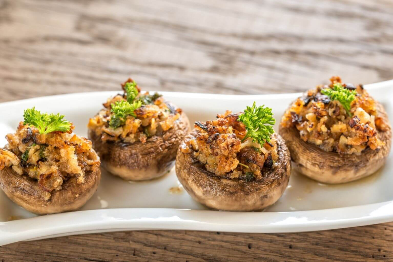 White rectangular plate with four stuffed mushrooms on top on a wooden table.