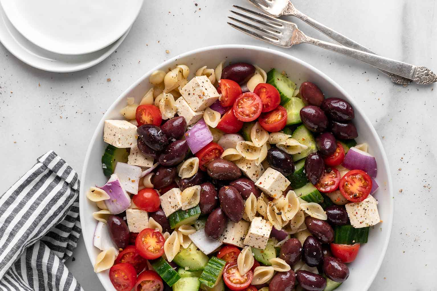 Greek pasta salad with olives, cucumber, tomato, feta in a white bowl