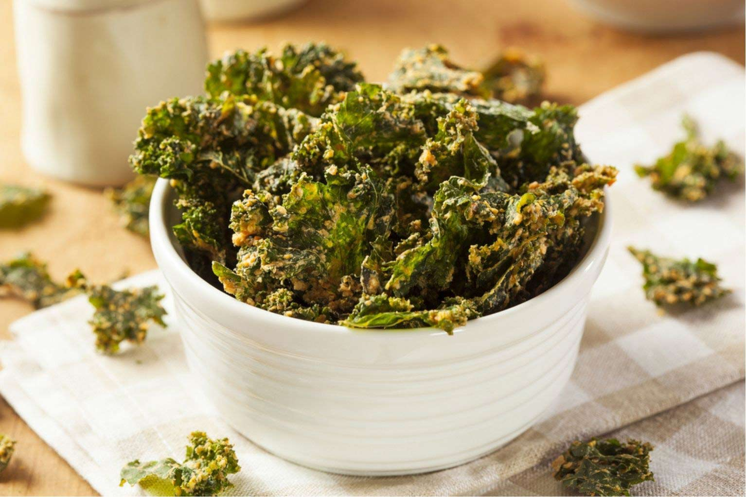 White ceramic cup full of kale chips seasoned with vegan cheese and seasoning.
