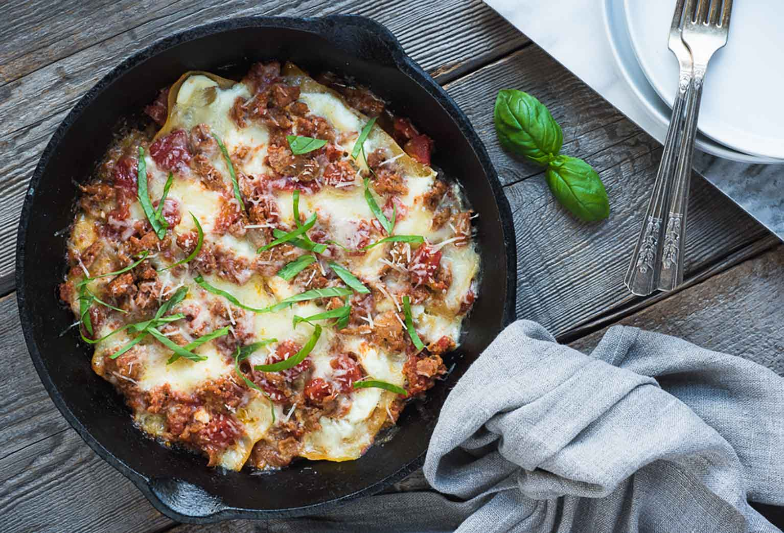 Skillet lasagna topped with basil and cheese in a cast iron pan