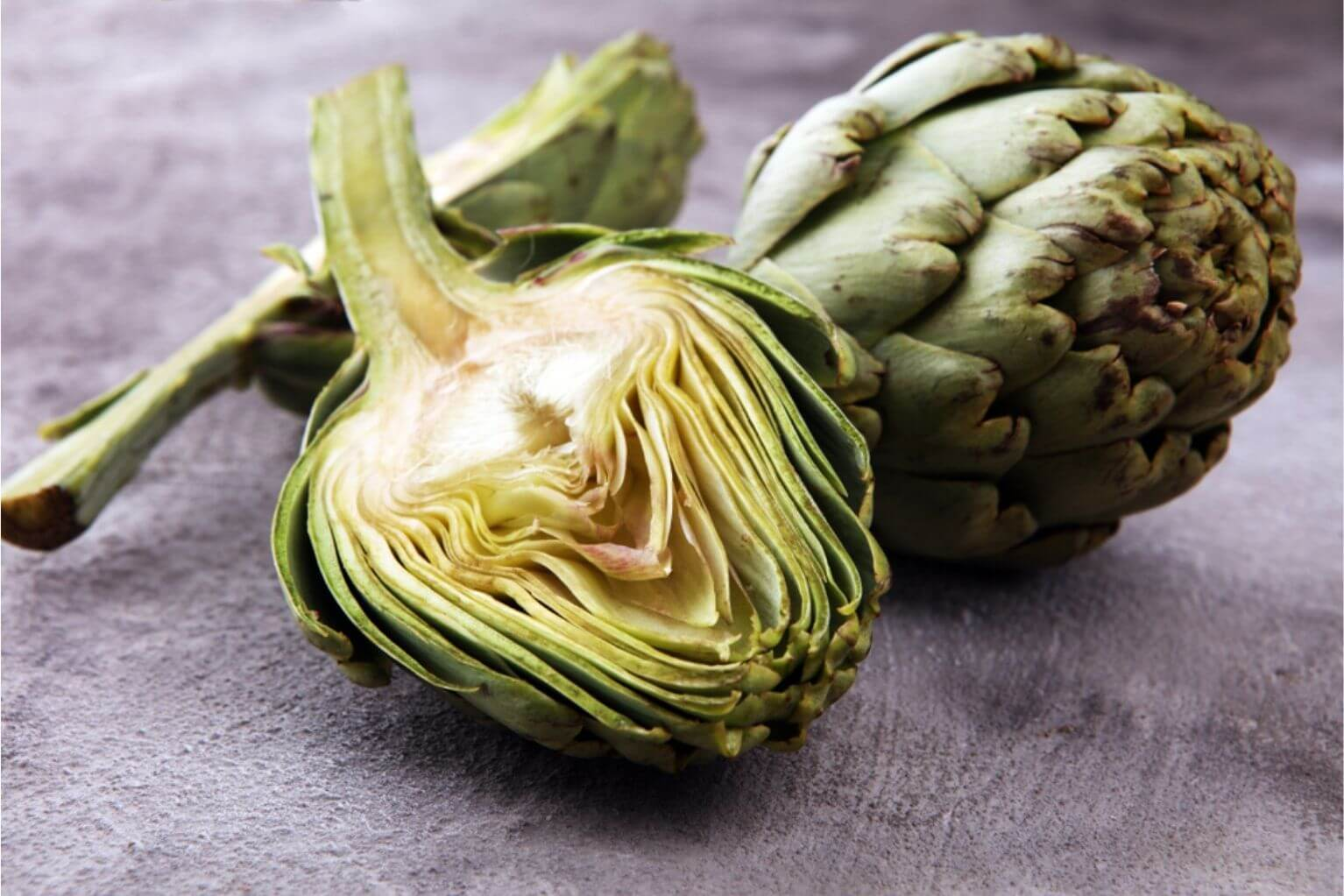 Two artichokes on a wooden table with one sliced in half.