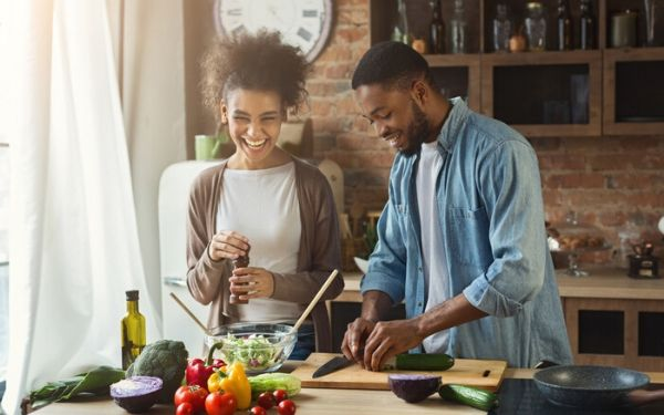 Young couple cooks a healthy meal together in their kitchen