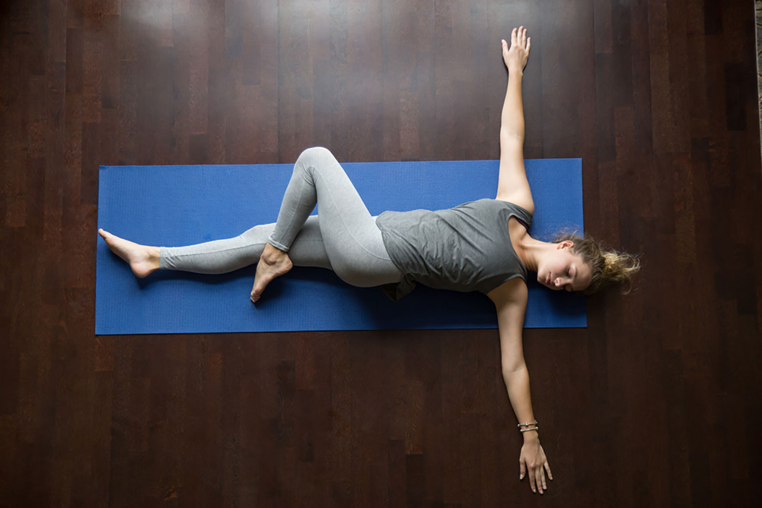 Young woman practicing the supine twist yoga pose
