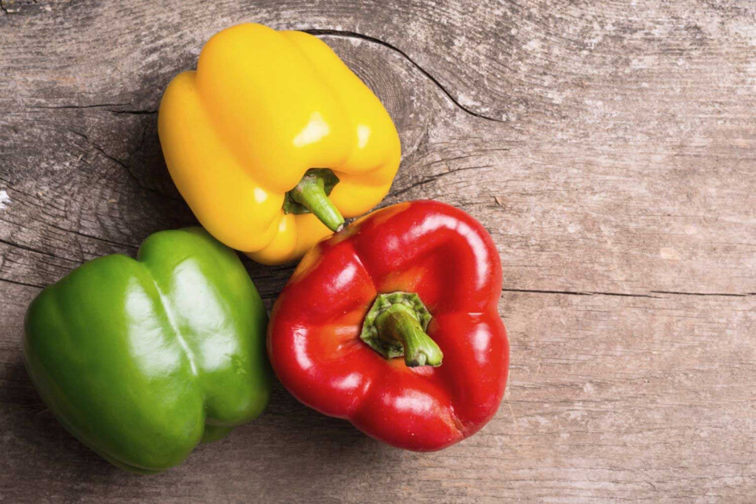 A green bell pepper, a yellow bell pepper and a red bell pepper sitting on a wooden table.